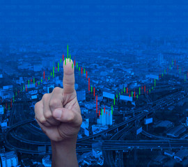 Hand pressing to trading graph of stock market over modern city tower, street, expressway and skyscraper, Business investment concept