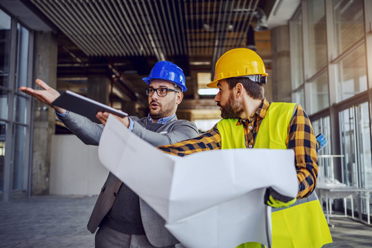 Upset architect arguing with construction worker and showing him his mistake. Worker holding blueprints and defending himself. Building in construction process interior.