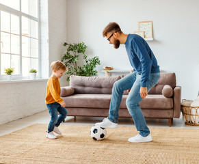 Father and son playing football in cozy room.