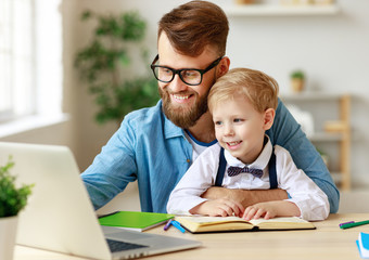 Father helping child with online lesson at home.