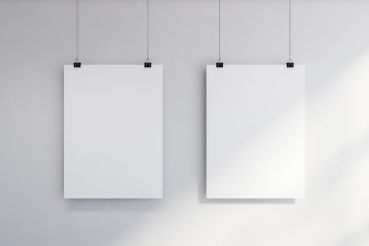 Two vertical mock up posters on white wall