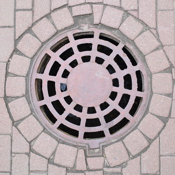 A metal manhole cover with openwork slots