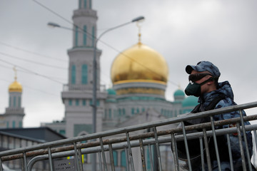 A law enforcement officer stands guard outside the closed Moscow Cathedral Mosque during Eid al-Fitr, the Muslim festival marking the end the holy fasting month of Ramadan, in Moscow