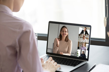 Back view of female employee have webcam conference conversation with diverse coworkers on laptop,...
