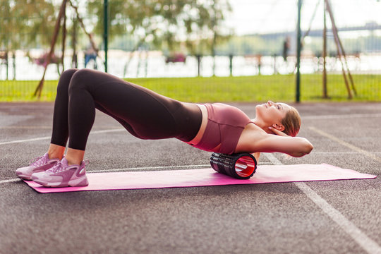 Fit blond woman training on mat outdoor summer day, using foam roller massager on her shoulders for relaxation, stretching spine muscles, doing fascia exercise. Health care, workouts routine side view