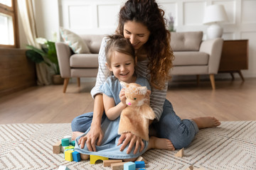 Smiling mother and little daughter hugging, playing with toys, sitting on warm floor with underfloor heating in living room, happy young mum and preschool girl enjoying leisure time together