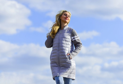 Windy day. Woman enjoying cool weather. Freshness of wind. Matching style and class with luxury and comfort. Beauty and fashion look. Girl jacket cloudy sky background. Woman fashion model outdoors