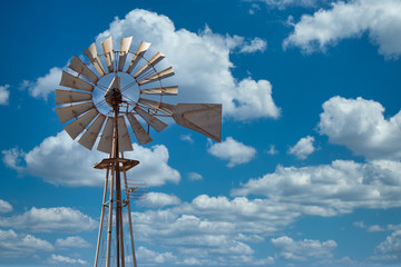 Image of old metal Wind mill against a blue sky