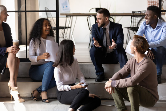 Happy successful business team sitting on stairs in office, having fun at work, diverse coworkers chatting, laughing at colleagues joke, positive employees enjoying break at work together