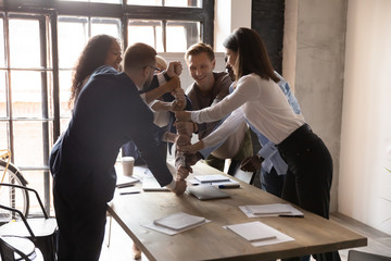 Excited business people stacking fists at table, engaged in team building activity at corporate...