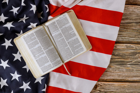 Open is reading Holy Bible book with prayer for america over ruffle American flag in wooden table