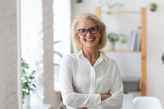 Portrait of smiling senior businesswoman in glasses standing posing in modern office, happy confident middle-aged female employee or CEO look at camera show confidence and success at workplace