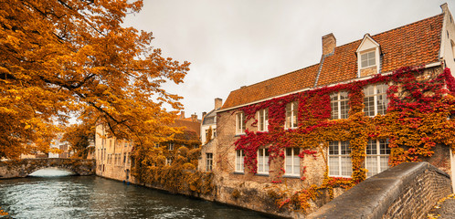 Wall Murals Bridges Panoramic view of beautiful canal with bridge and houses of Brugges, Belgium in autumn. Banner edition. Selective focus.