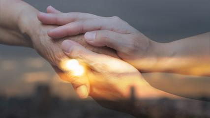 Caregiver, carer hand holding elder hand in with city urban background. Philanthropy kindness...