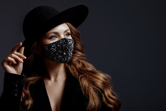 Elegant woman wearing trendy fashion outfit during quarantine of coronavirus outbreak. Black suit including stylish luxury face safety mask with rhinestones. Close up portrait. Copy, empty space
