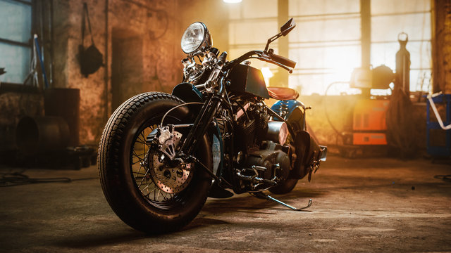 Custom Bobber Motorbike Standing in an Authentic Creative Workshop. Vintage Style Motorcycle Under Warm Lamp Light in a Garage.