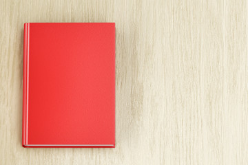 Red book on wood background