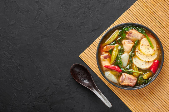 Sinigang na Baboy or Filipino Pork Meat Soup in black bowl on dark slate backdrop. Sinigang - Filipino cuisine dish with meat, bamia, daikon, spinach, fish sauce. Filipino Food. Asian Meal. Copy space