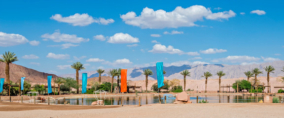 Tropical oasis and beach with palm trees and artificial lake in green oasis in stone desert among surrounding mountains