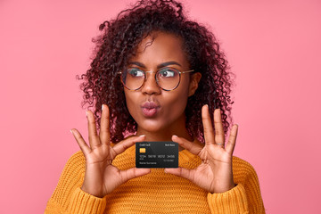 Portrait of young pretty african american woman depicting kiss holding bank credit card in hands, going to buy something in an online store, over pink studio background. Place for advertising