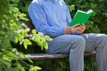 Relaxed businessman reading a green book on a park bench