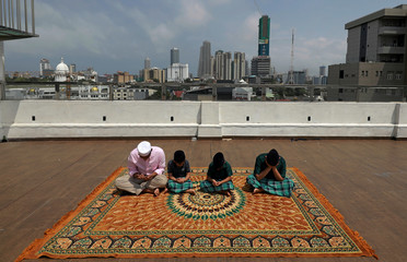Kids of a Muslim family prays at a rooftop of their residence during the Eid al-Fitr prayers to mark the end of the holy fasting month of Ramadan in Colombo