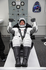 NASA astronaut Robert Behnken rehearses putting on his SpaceX spacesuit in the Astronaut Crew Quarters