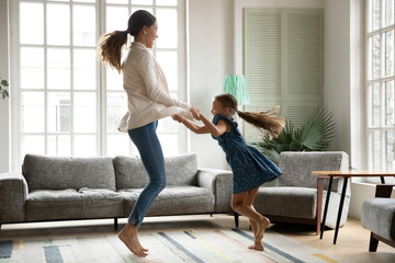 Overjoyed young mom or nanny have fun jumping in living room with excited small girl child, happy playful Caucasian mother dancing relaxing with smiling little daughter, enjoy family weekend at home