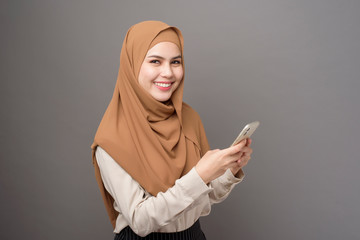 Portrait of beautiful woman with hijab using cellphone on gray background