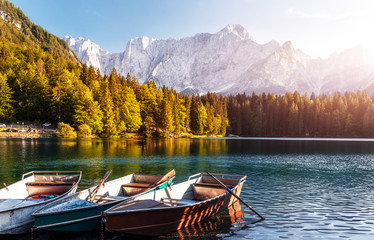Fotomurales - Beautiful view on Fusine lake side. Scenic image of fairy-tale lake with boats on water and colorful sky. Wonderful Autumn scenery. Amazing nature Background. Awesome dramatic scene. Julian Alps