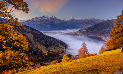 Fotomurales - Incredible Nature Landscape., foggy morning during sunrise at Alpine lake in autumn. Colorful Sky over the Zeller Lake in Zell am See, Salzburger Land, Austria. Creative image. Natural Background