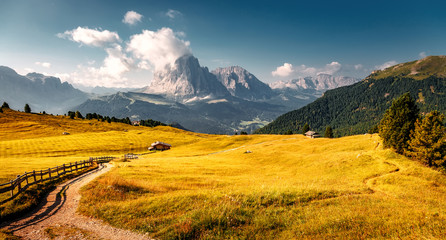Fotomurales - Beautiful alpine countryside. Awesome Alpine landscape with traditional huts. Amazing Nature Scenery of Dolomites Alps. Epic Scene in the mountains place near Seceda peak. Val Gardena. Dolomiti alp