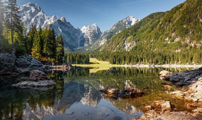 Fotomurales - Scenic image of Fairytale lake Fusine during sunset. Picturesque landscape with lake, forest and majestic mount. Wonderful Autumn landscape. Picturesque view of nature. Amazing natural Background