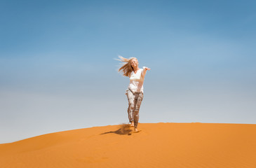 Sporty woman in Merzouga dunes of Sahara desert Morocco Africa. Travel and inspiration concept
