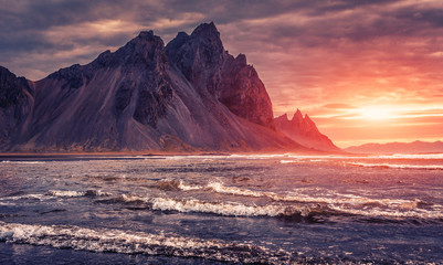 Foto auf Gartenposter Aubergine lila Impressive Colorful Seascape of Iceland. Wonderful picturesque Scene. Dramatic colorful sky glowing sunlit. Wonderful view of nature. Best popular places near Stokksnes cape and Vestrahorn Mountain.