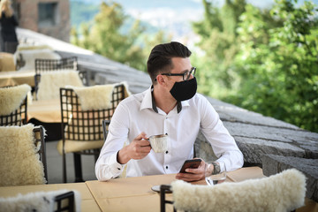 Young fashion Businessman with face mask drinking espresso coffee in the city cafe during lunch time and working on smartphone