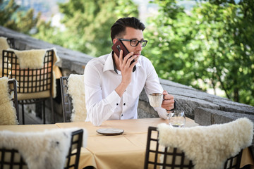 Young fashion Businessman drinking espresso coffee in the city cafe during lunch time and working on smartphone