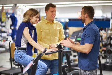 young caucasian customers came in sportswear store to make purchase, handsome guy and woman get...
