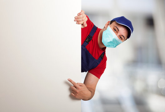 Masked worker pointing his finger to a blank board