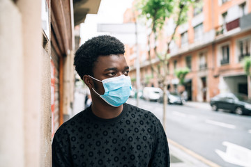 African-American black guy walking down the street with a mask on his face