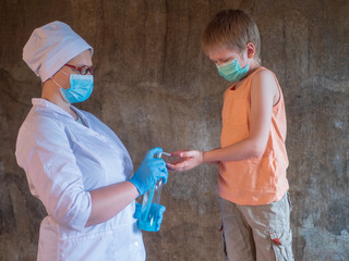 Family with child in mask on gray background. Mother in white coat and baby wear face mask during coronavirus and flu outbreak. Protection against viruses and diseases, hand sanitizer in public places