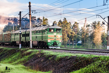 Russia, Gatchina, may 16, 2020: a Freight train rides on the rails. Smoke billows from the locomotive.