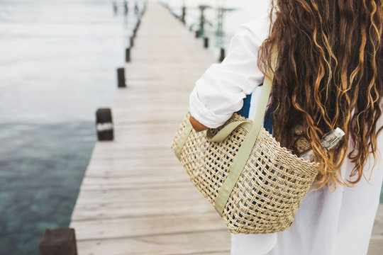 Woman with handmade wicker bag, two beach towels and glass bottle for water going to the beach. View from behind close up. Eco friendly and zero waste concept.