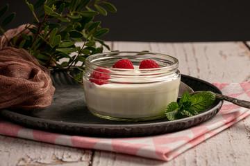 Yoghurt with raspberries on a metal plate