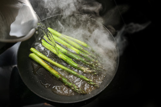 Green asparagus in a frying pan is poured with water, that produces a lot of steam, black stove with copy space