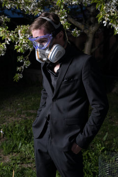 Young man portrait in mask with degree of protection 3M posing in twilight of spring garden.