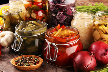 Fototapeta Preserves vegetables in glass jars. Pickled Cucumber, carrot, fermented cabbage and onions on rustic background obraz