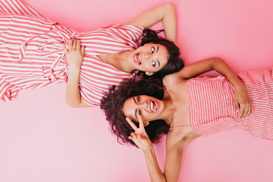 Funny girls fool around and show tongues while posing on pink background. Ladies in striped dresses lie on floor
