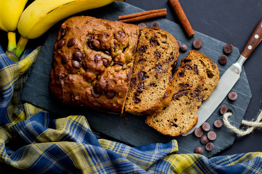 Banana bread with chocolate chips with a plaid napkin and dark background