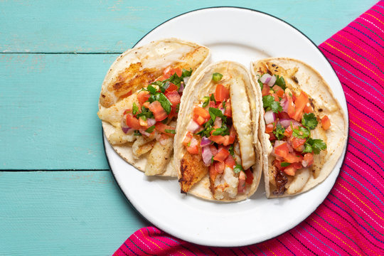 Mexican fish tacos also called Baja with fresh sauce on turquoise background
